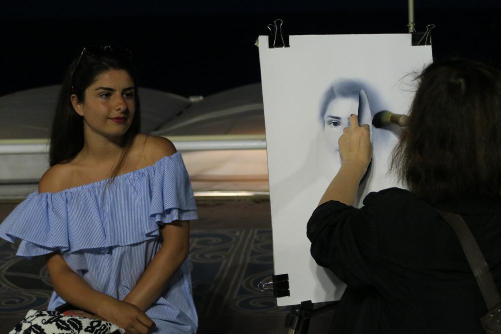 夜のプロムナード・デ・ザングレ似顔絵を書いている